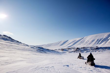 Two snowmobiles on a barren winter landscape, Svalbard Norway photo