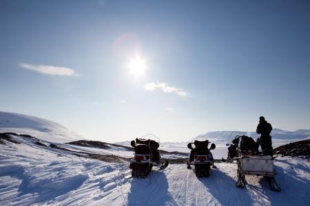Three snowmobiles on a Svalbard Landscape - winter adventure photo