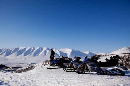 Snowmobiles in a barren winter landscape, Svalbard, Norway photo