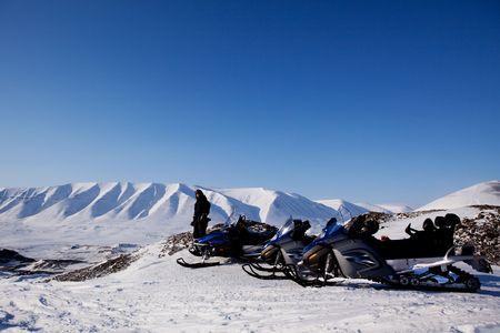Snowmobiles in a barren winter landscape, Svalbard, Norway photo