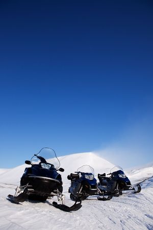 Three snowmobiles on an outdoor winter landscape photo
