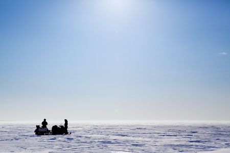 spitsbergen: A barren flat winter landscape with two people and snowmobiles Stock Photo