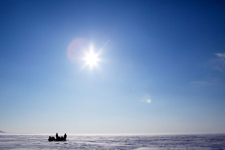 Two snowmobiles on a frozen lake in winter photo