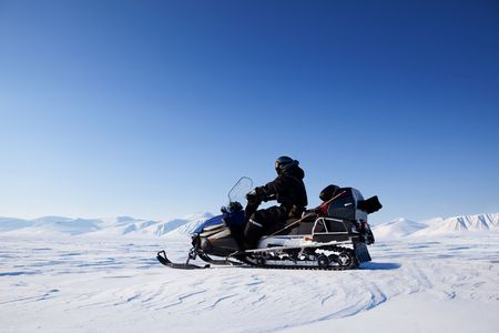 A snowmobile on a frozen lake against a winter landscape with mountains photo