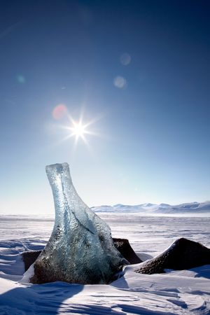 A piece of glacier ice sticking out of the frozen ocean, Spitsbergen, Svalbard, Norway photo