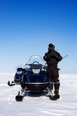 An expedition guide and a couple of snowmobiles on a winter landscape photo