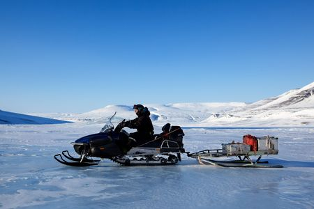 A man on a snowmobile against a winter landscape photo