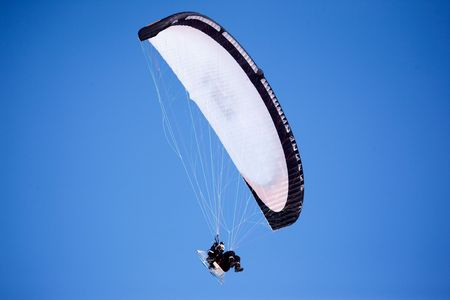 A paraglider isolated against a deep blue sky photo