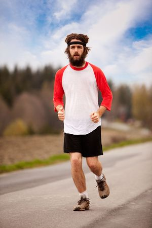 vintage style: A tired retro style jogger running on a road outdoors