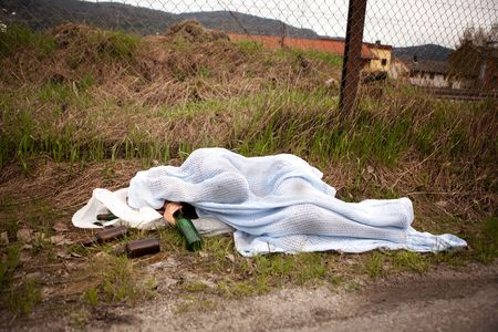 dirty man: A homeless drunk person sleeping in the ditch Stock Photo