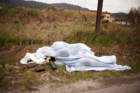 hombre pobre: Una persona sin hogar durmiendo borracho en la zanja Foto de archivo