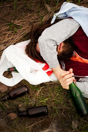 A drunk person sitting in a ditch with a wine bottle Stock Photo - 5693537