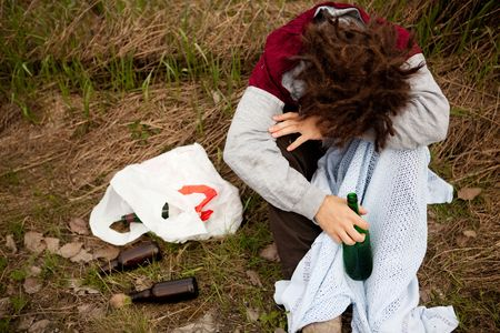wino: A drunk person sitting in a ditch with a wine bottle Stock Photo