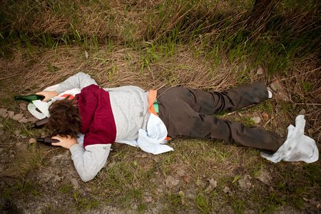 A drunk homeless man laying the ditch photo