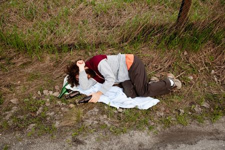 Passed out: A drunk laying in the ditch with a number of bottles Stock Photo