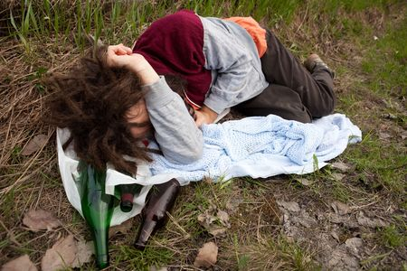 tramp: A drunk passed out in the ditch with a bunch of alcohol bottles Stock Photo