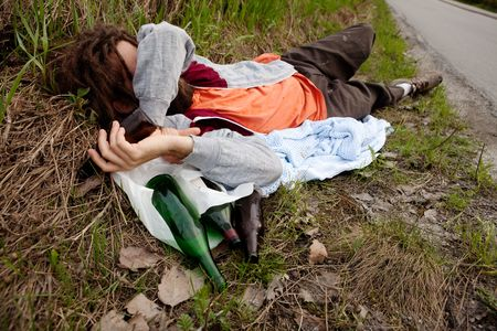 A drunk man laying in the ditch with beer bottles photo