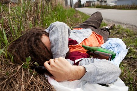 A homeless drunk person laying by the edge of the road photo