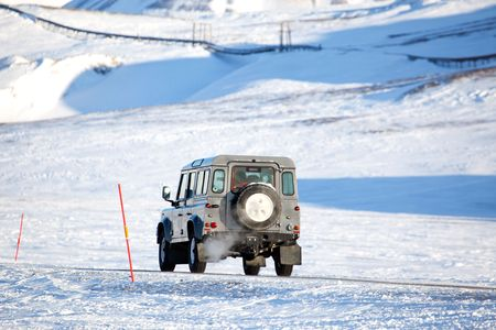 spitsbergen: A truck driving on a barren landscape of snow and ice - Svalbard, Norway