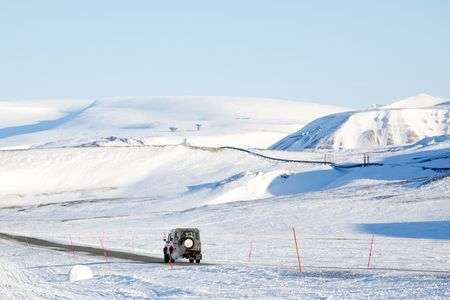 A truck driving on a barren landscape of snow and ice - Svalbard, Norway photo