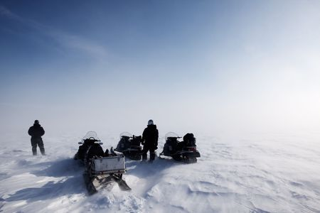 A blowing snow landscape with three snowmobiles on an expedition Stock Photo - 5702316