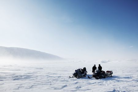 Three snowmobiles on a winter landscape with blowing snow photo