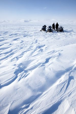 expedition: A barren winter landscape with a group of people on a snowmobile expedition