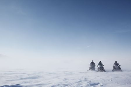arctic landscape: Three snowmobiles on a blowing barren winter landscape