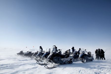 A group of snowmobiles travelling accross a barren winter landscape photo