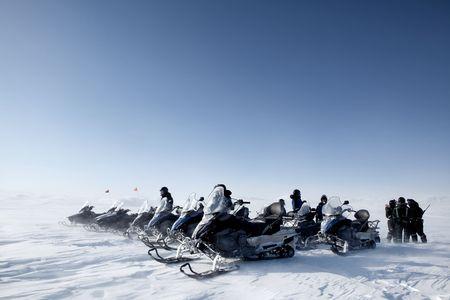 nieużytki: Grupy śniegowych podróżowania po surowym krajobrazie zimowym Zdjęcie Seryjne
