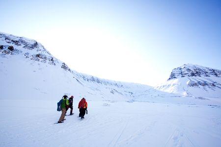 A group of people treking across a winter landscape photo