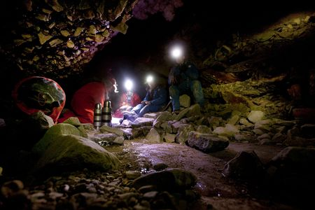 headlamp: A group of people eating lunch in a dark cave