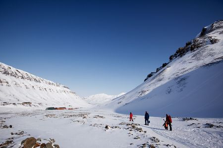 svalbard: A group of people walking along a path ouside Longyearbyen, Spitsbergen, Svalbard, Norway