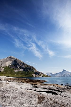A coastal landscape in northern norway with a mountain and rock photo