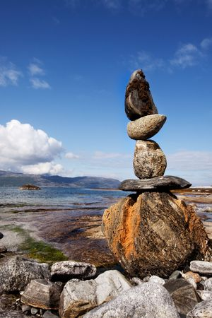 obelisk stone: A rock stacking sculpture statue on a Norwegian landscape