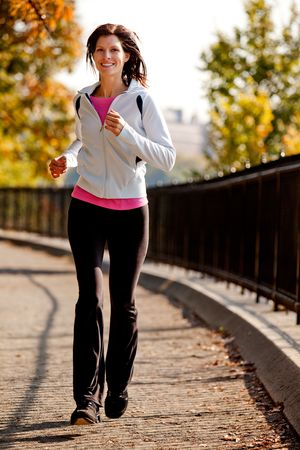 A young woman jogging on a path in a park Stock Photo - 5802492