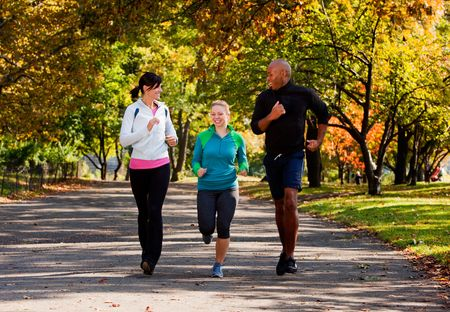 Three young adults jogging in the park photo