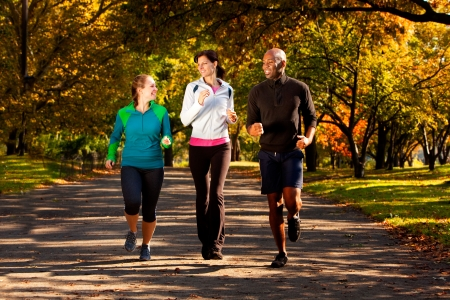 Three people jogging in the park on a beautiful fall day photo