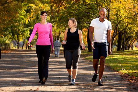Tres personas caminando en un parque, hacer algún ejercicio