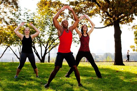 man jump: A group of people doing jumping jacks in the park Stock Photo