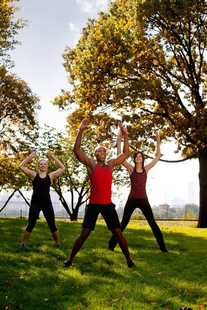 jacks: A group of people doing jumping jacks in the park Stock Photo
