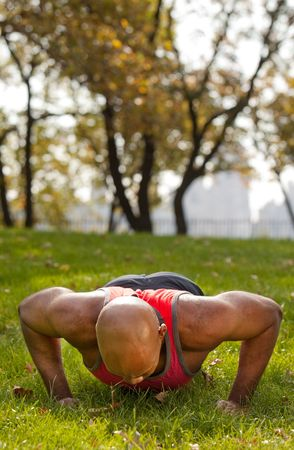 push ups: An african american male doing push ups in a park Stock Photo