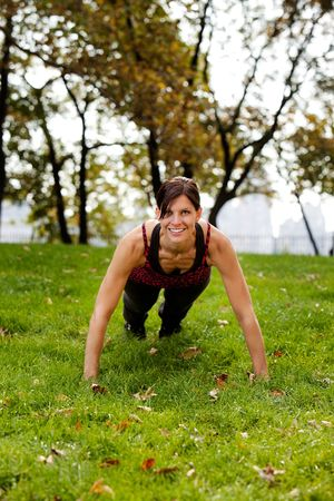 A caucasian female doing push ups in the park Stock Photo - 5802432