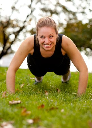 A woman doing push-ups in the park photo
