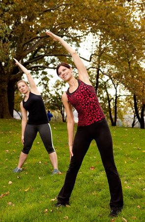 A group of people stretching in a park - focus on front woman photo
