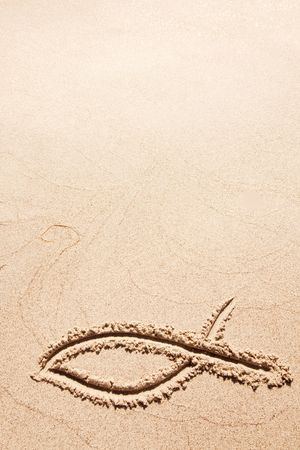 sand drawing: A fish symbol in drawn in the sand