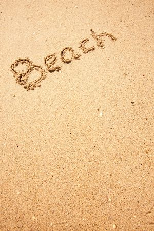Beach written in the sand on the coast with mountains in the background photo