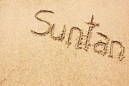 The word suntan written in the sand on a beach photo