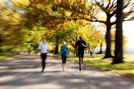 Three people jogging in the park with zoom blur photo