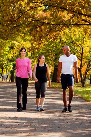 outdoor walking: Three people walking in a park, getting some exercise Stock Photo